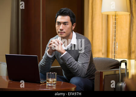 Young businessman thinking in hotel room Banque D'Images