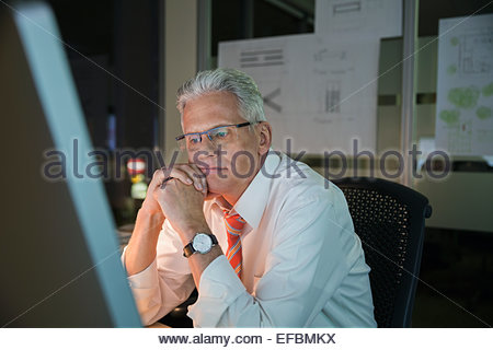Pensive businessman travaillant tard at computer in office Banque D'Images