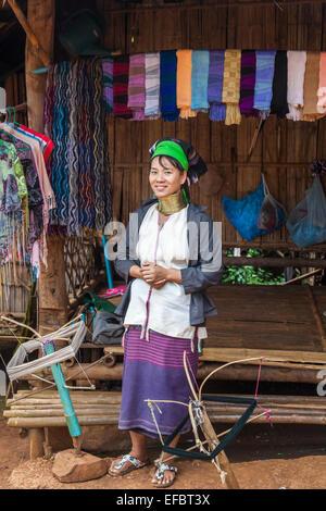 Jeune femme birmane long cou debout à l'extérieur un tissu d'une boutique de souvenirs dans une hutte dans village Banque D'Images