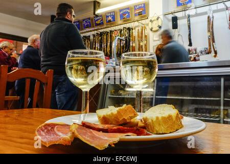 Deux verres de vin blanc, pain, jambon et chorizo tapas sur une table de bar, Benidorm, Costa Blanca, Espagne. Banque D'Images