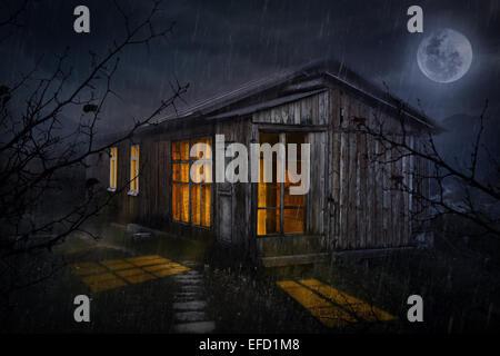 Maison rurale avec windows rougeoyant dans la nuit in the sky Banque D'Images
