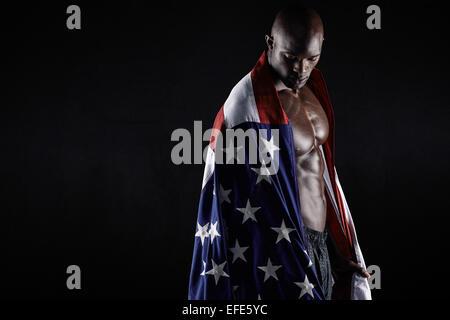 Portrait d'homme musclé enveloppé dans le drapeau américain avec l'exemplaire de l'espace sur fond noir. Athlète Banque D'Images