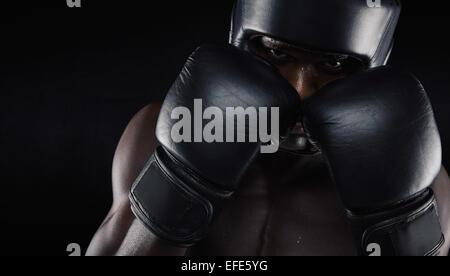 Boxeur afro-américain avec des protections contre l'arrière-plan noir. Jeune homme l'exercice de la boxe.