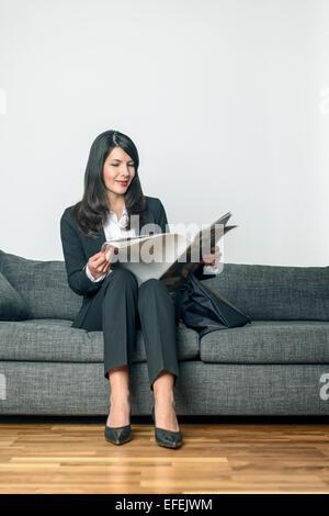 Attractive businesswoman dans un élégant costume mou en train de lire un journal ou un journal d'affaires sur un Banque D'Images