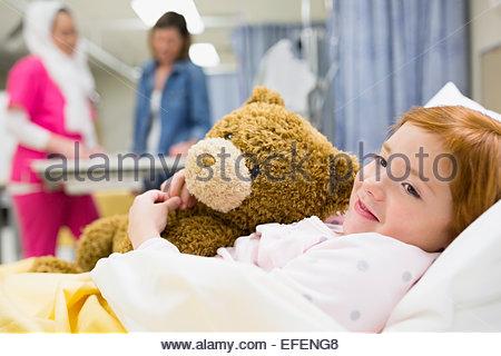 Girl hugging teddy bear in hospital bed Banque D'Images