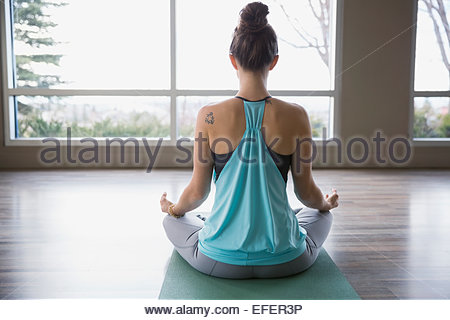 Rear view of woman meditating in lotus position Banque D'Images