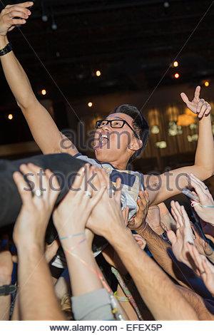 Homme enthousiaste en tenant tout en concert à crowdsurfing selfies Banque D'Images