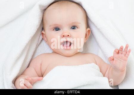 Cute smiling baby portrait couché sur une serviette de bain Banque D'Images