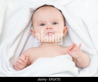 Cute funny bébé dans une serviette de bain montrant langue maternelle Banque D'Images