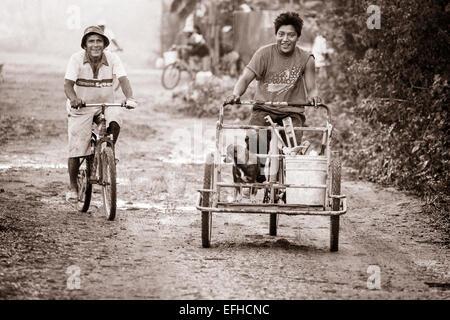Début au travail: outils et un chien: monochrome. Les travailleurs de la construction par des bicyclettes à leurs Banque D'Images