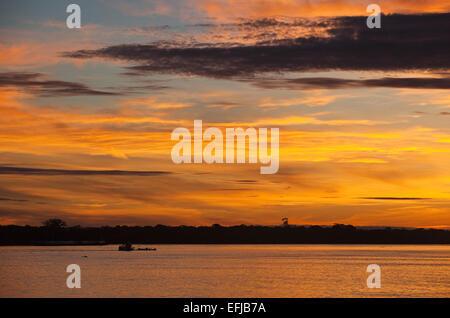 Le lever du soleil sur le fleuve Amazone à 6h avec bien river bank silhouetted against orange rouge et jaune spectaculaire Banque D'Images