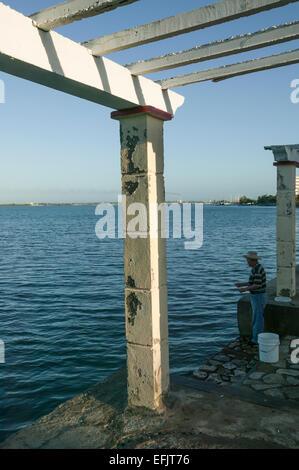 La pêche de la côte de l'homme cubains tout en vous tenant à côté d'un axe le long de la baie de Cienfuegos, Punta Banque D'Images