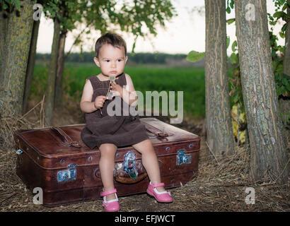 Cute little girl blowing dandelion sur une valise à l'extérieur Banque D'Images
