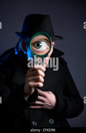 Man in black hat avec loupe en à l'arrière-plan noir Banque D'Images