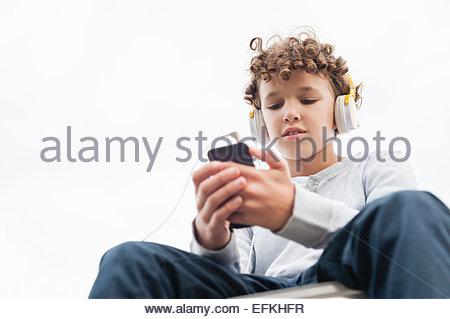 Garçon assis sur le rebord, portant des écouteurs et l'aide de mp3 player Banque D'Images