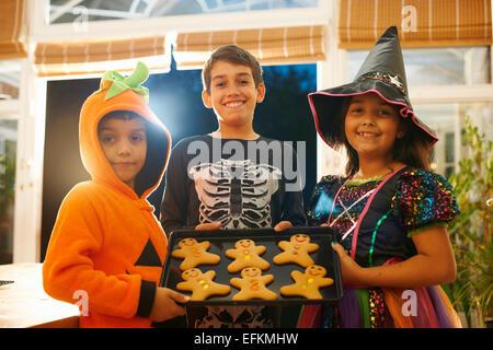 Frères et soeur portant des costumes de halloween holding tray of gingerbread men Banque D'Images