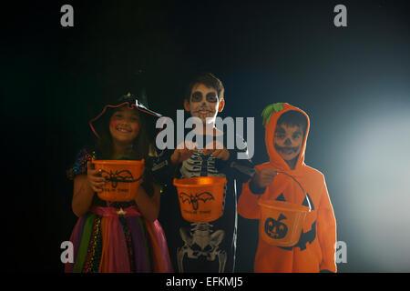 Portrait de frères et sœur portant des costumes de halloween holding trick ou traiter des seaux Banque D'Images