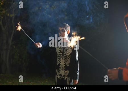 Boy wearing costume squelette halloween avec sparkler dans la nuit le jardin Banque D'Images