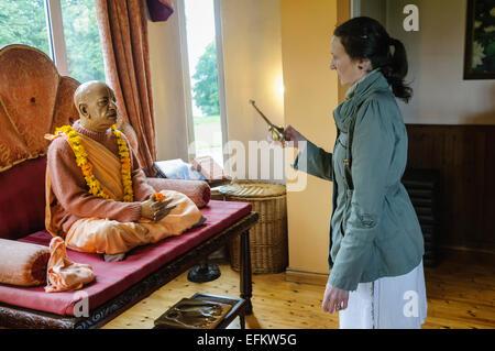 Une femme sprinkes la purification de l'eau sur la statue d'A.C. Bhaktivedanta Swami Prabhupada, fondateur du mouvement Hare Krishna (ISKCON) dans un temple prix