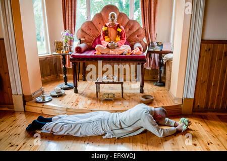 Un dévot Hare Krishna portant des robes blanches se prosterne devant la statue d'A.C. Bhaktivedanta Swami Prabhupada fondateur du Mouvement Hare Krishna.