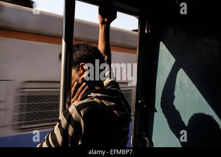 Un homme travaille sur un train de banlieue de Mumbai, Inde