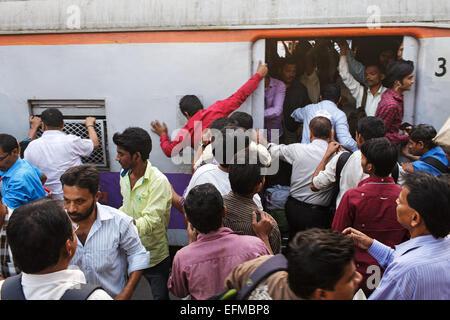 Les usagers du train d'embarquement pendant l'heure de pointe du soir à la gare de Bandra à Mumbai, Inde.