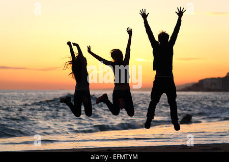 Trois silhouettes d'amis heureux de saut et d'élever les bras sur la plage au coucher du soleil Banque D'Images