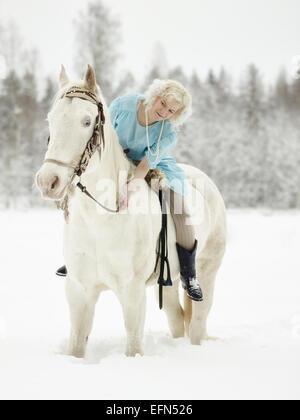 Attractive Woman wearing robe bleue et elle a un cheval blanc Banque D'Images