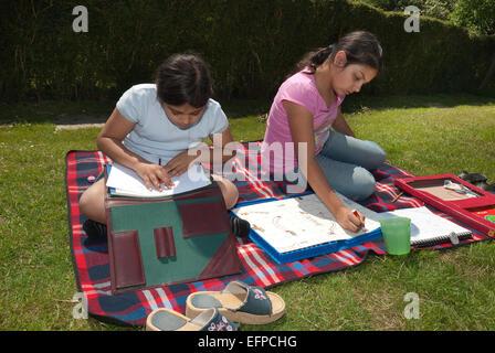 Se détendre au soleil deux jeunes filles s'amuser en faisant de l'artisanat et de l'écriture créative alors que Banque D'Images