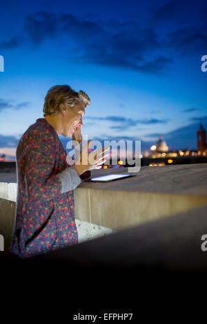 Young businesswoman using digital tablet tout en bavardant sur smartphone la nuit, Londres, UK Banque D'Images