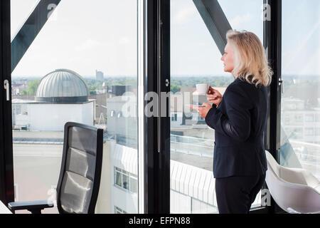 Businesswoman drinking coffee par fenêtre Banque D'Images