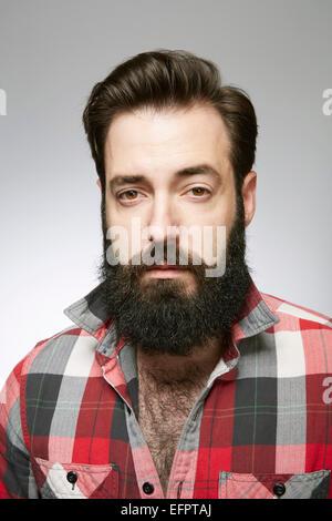 Studio portrait de jeune homme barbu à l'écart