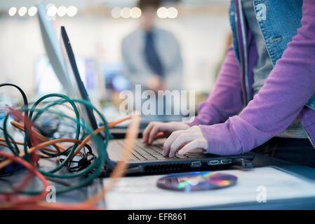 Une personne à l'aide d'un ordinateur portable. Disque et fils sur le comptoir. Atelier de réparation. Banque D'Images