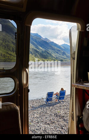 Vue depuis le camping-car porte de Mid adult woman sitting by lake, Palmer, Alaska, USA Banque D'Images
