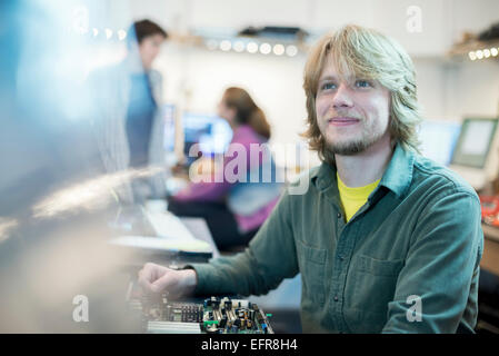 Un jeune homme et deux de ses collègues de travail dans un magasin d'informatique. Banque D'Images