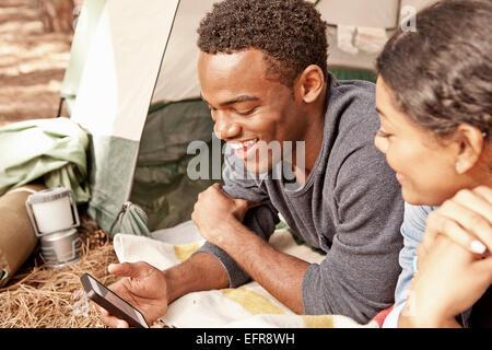 Jeune couple couché dans la lecture des textes du smartphone d'entrée de la tente