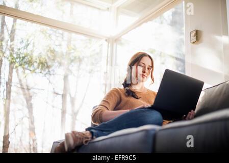 Portrait d'une femme assise sur un canapé en regardant son portable. Banque D'Images