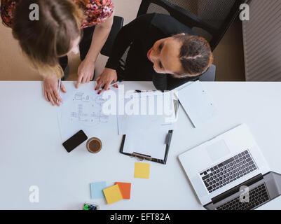 Vue supérieure de deux jeunes femmes travaillant ensemble sur un nouveau projet d'entreprise. Man sur un document Banque D'Images