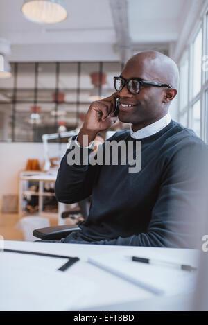 Jeune homme africain assis à son bureau à parler sur son téléphone portable dans le bureau. À l'aide d'Africains Banque D'Images