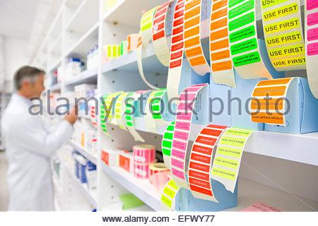 Les étiquettes en premier plan et de pharmacien à la pharmacie sur les médicaments Banque D'Images