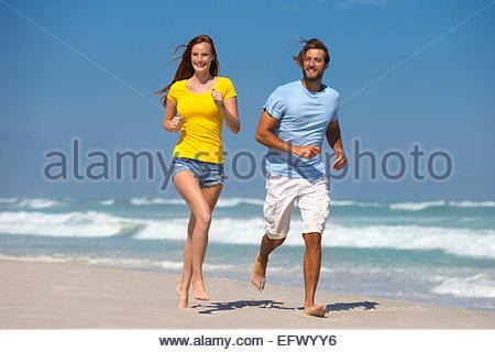 Couple heureux, souriant et s'exécutant sur sunny beach Banque D'Images