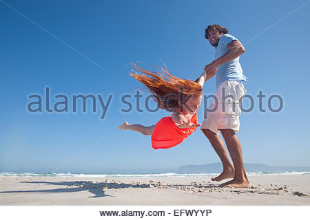 Smiling Father swinging fille jouant autour sur sunny beach Banque D'Images
