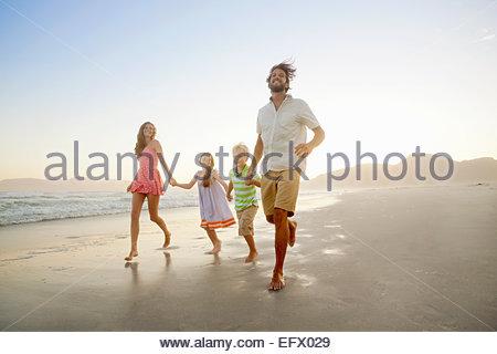 Famille heureuse, tenant les mains, s'exécutant sur sunny beach Banque D'Images