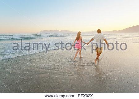 Couple, se tenir la main, marcher à travers les vagues sur la plage ensoleillée Banque D'Images
