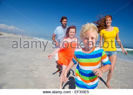 Famille heureuse de courir vers l'appareil photo, on sunny beach Banque D'Images