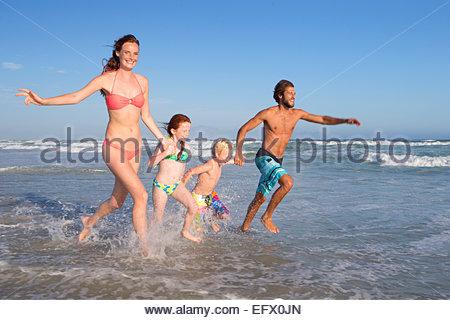 Famille heureuse dans le bain d'exécution à travers les vagues, se tenir la main, on sunny beach Banque D'Images