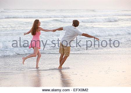 En couple, en se tenant la main, tournant à travers les vagues sur la plage ensoleillée Banque D'Images