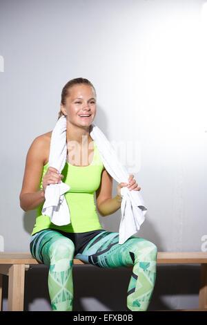 Jeune femme assise sur un banc en prenant une pause dans la salle de sport Banque D'Images