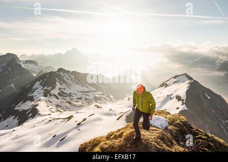 Jeune homme trekker sur la montagne haut de ridge dans Alpes bavaroises, Oberstdorf, Bavière, Allemagne Banque D'Images