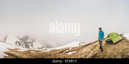 Vue panoramique du jeune homme et tente dans la brume, Alpes bavaroises, Oberstdorf, Bavière, Allemagne Banque D'Images